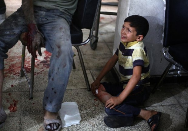 A Syrian boy cries as he looks at his wounded father on September 9, 2014
