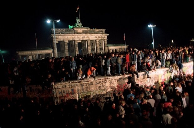 Berliners crowd atop the Berlin Wall near the Brandenburg Gate on 11 November 1989