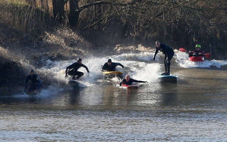Surfers ride the Severn bore at Minsterworth, southwest England on March 21, 2015