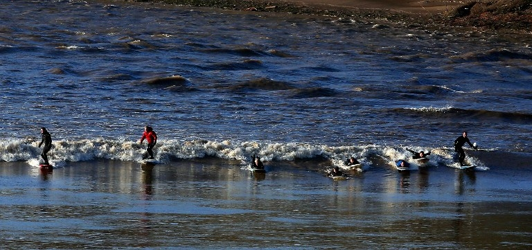 Surfers ride the Severn bore at Newnham, southwest England on March 21, 2015