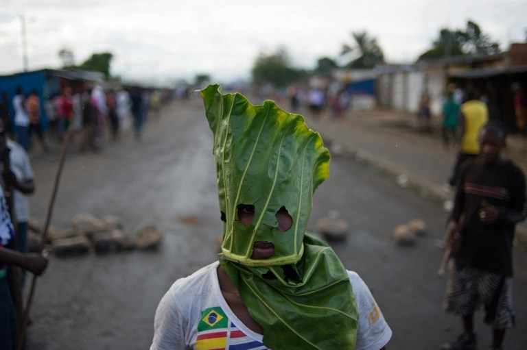 A Burundian protester wearing a gas mask chants near a burning barricade in the Mugasa neighbourhood of Bujumbura on May 6, 2015
