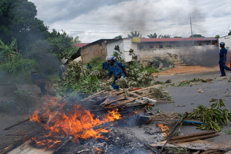 Shortly after firing shots, Burundian police clear a barricade hastily erected by protesters in the city centre in Bujumbura on May 6, 2015