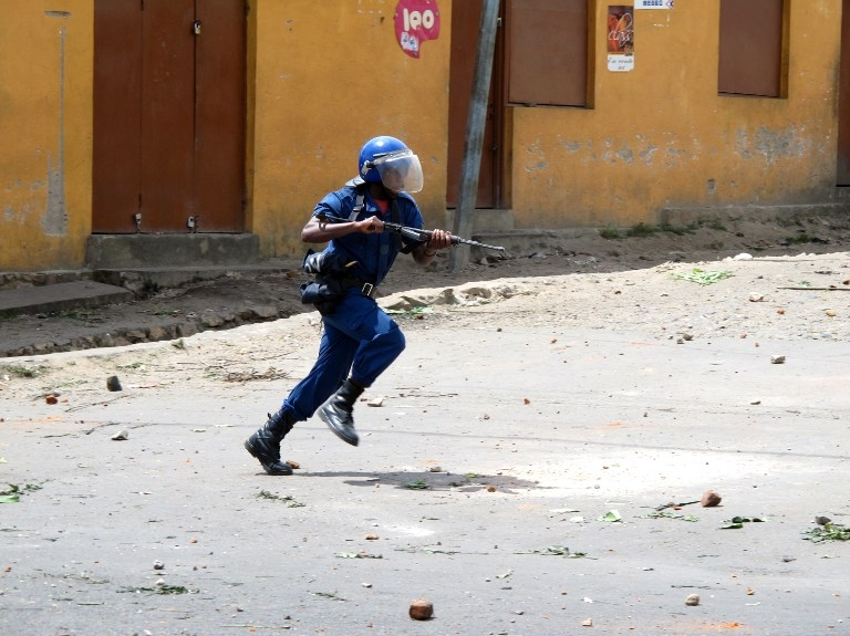 A policeman runs during clashes with protesters in Bujumbura on May 4, 2015