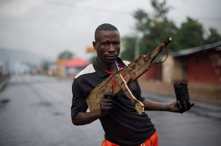 A man poses with a wooden rifle in the Musaga neighbourhood in Bujumbura on May 5, 2015