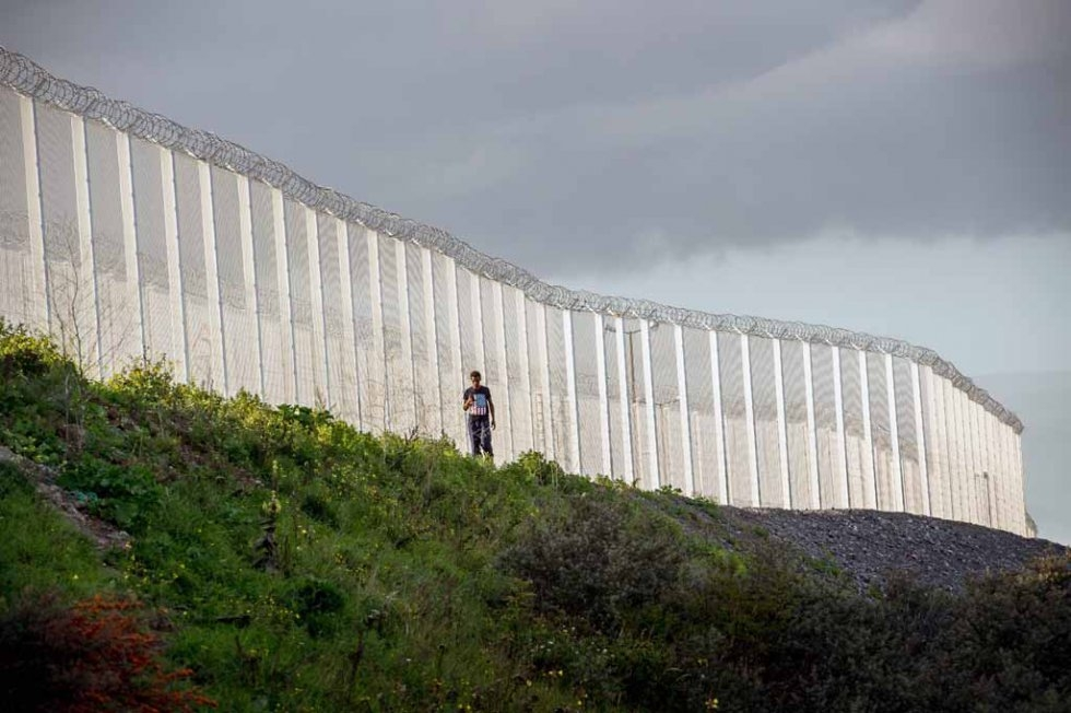 A migrant walks along the fence built to keep refugees away from the port (AFP/Philippe Huguen)