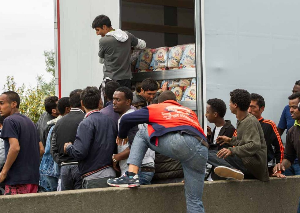 Migrants hop onto a truck heading for England
