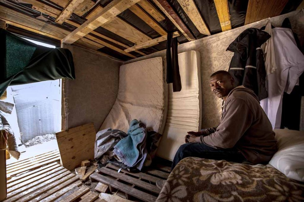Migrant from Sudan takes cover from rain inside a makeshift hut