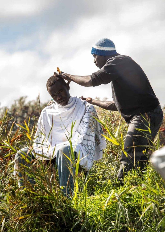 A migrant cuts a fellow refugee's hair