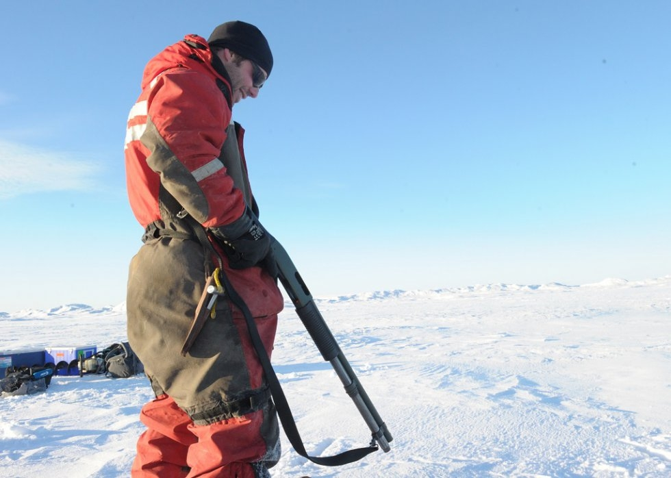 Sailor Hugo Jacques guards against polar bears as scientists work on the ice