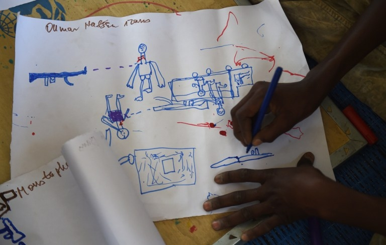 A Young Nigerian refugee draws an attack scene during a workshop at a camp near Baga Sola on April 6, 2015