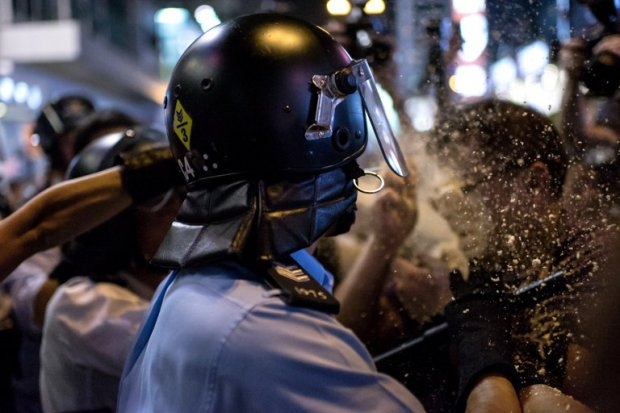 A local Hong Kong journalist (R) is pepper sprayed by police in the Mongkok district of Hong Kong on October 17, 2014 (AFP Photo / Alex Ogle)