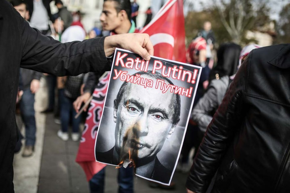A protester sets fire to a Putin poster during a demonstration against Russia in Istanbul, November, 2015.