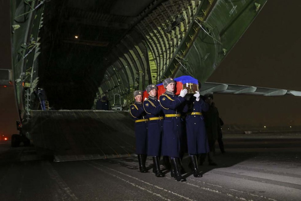 Russian honour guards carry the coffin with the body of one of the pilots from the shot-down plane.