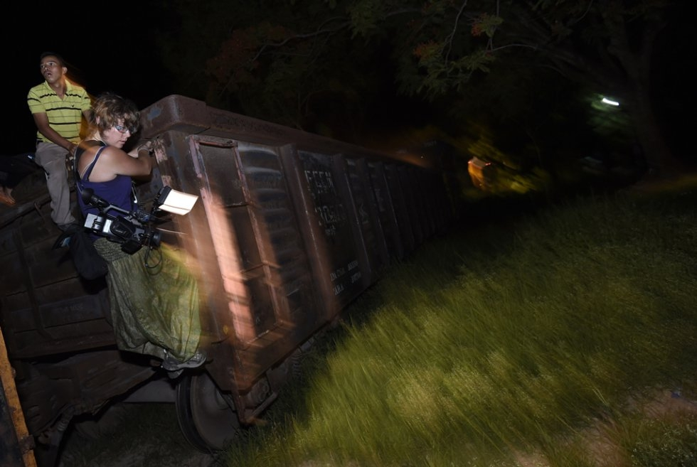 AFP reporter Daphne Lemelin jumps from a train in Palenque, Chiapas State after filming migrants on board on June 20, 2015