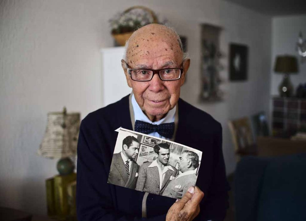 Don Neto holds a photo of himself