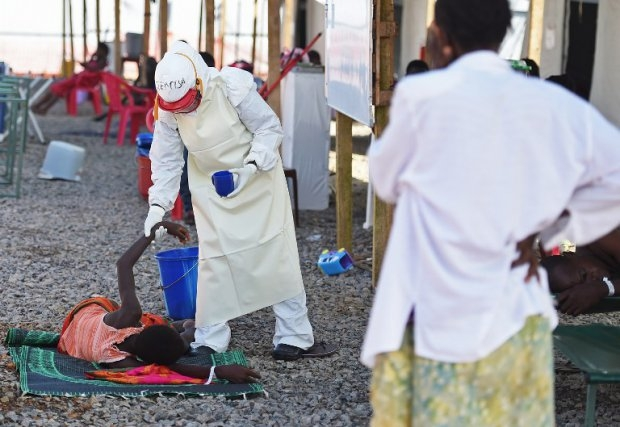 A health worker assists an Ebola patient at the Kenema treatment center