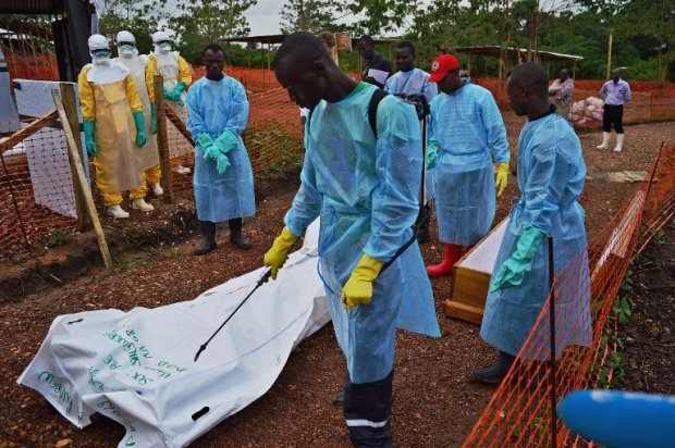 Sierra Leonese government burial team members disinfect the body bag of an Ebola victim at the Medecins Sans Frontieres