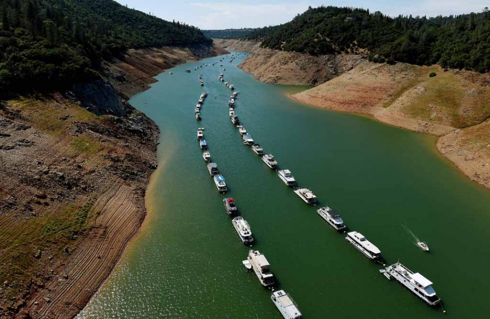 Houseboats are moored on a shrinking arm of a California lake. May, 2015.