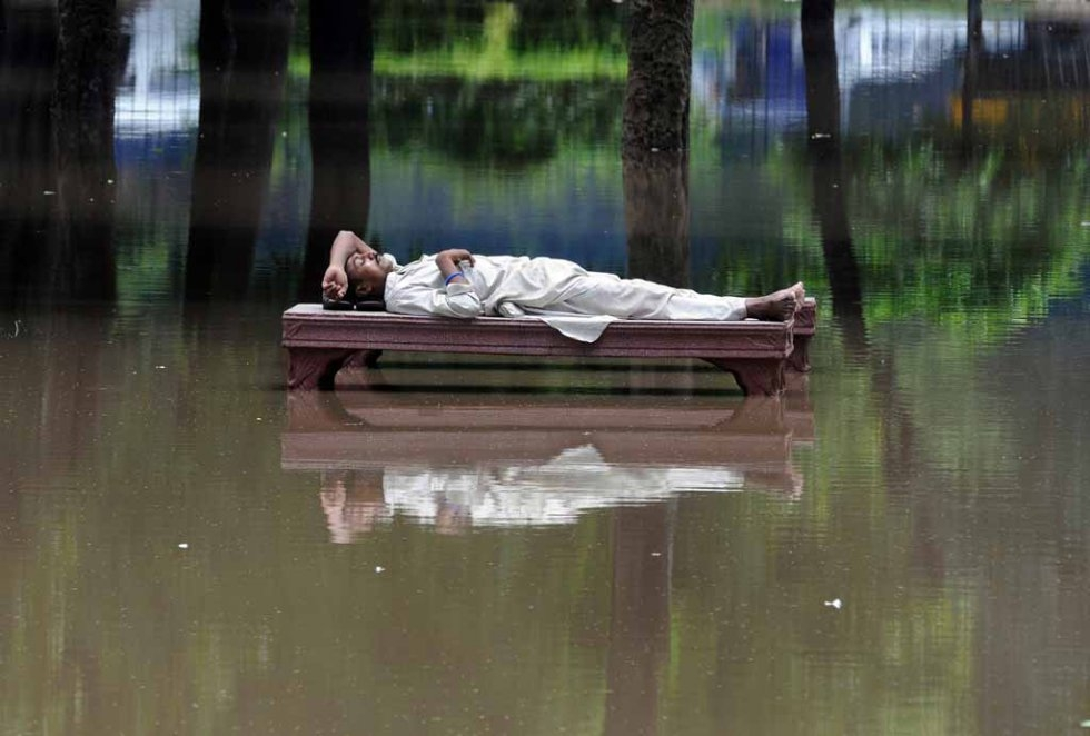A man rests on a bench amid floodwater in Lahore, Pakistan. July, 2008.