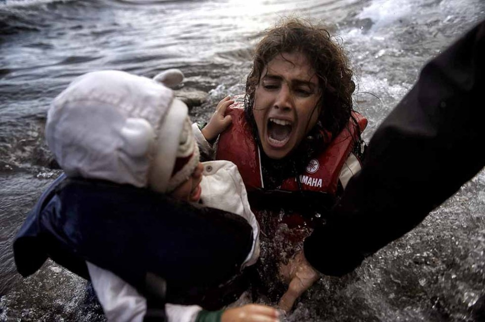 A woman falls into the water with her child at a Lesbos beach after crossing the Aegean sea from Turkey in October. (AFP/Aris Messinis)