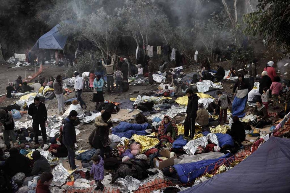 Refugees and migrants wake up after spending a night in a Lesbos field in early October.