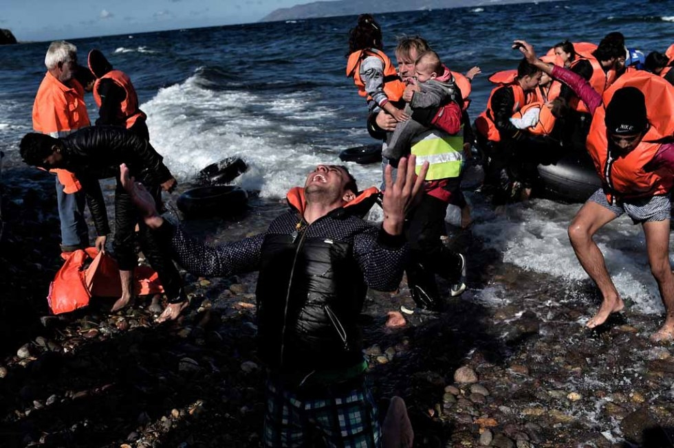 A man falls to his knees as he gets to Lesbos in late October.