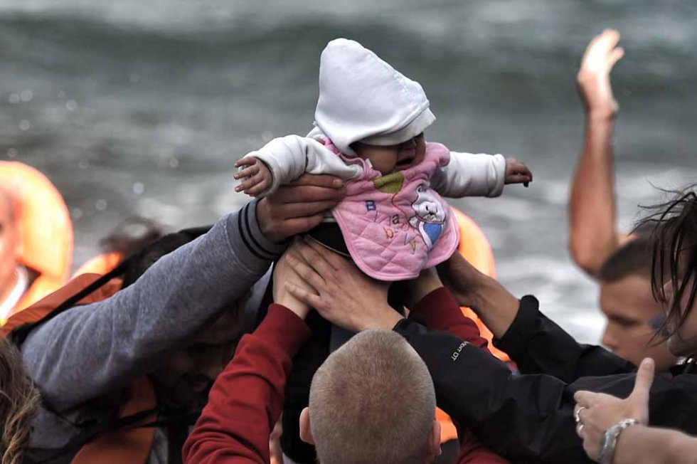 A baby is passed from hand to hand after arriving in Lesbos in late October.