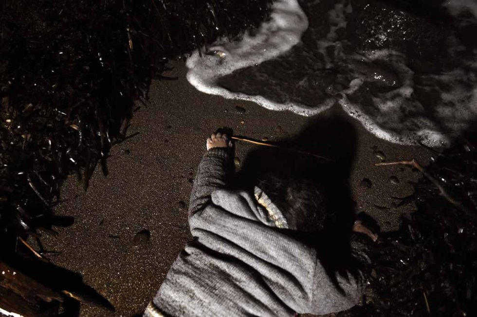 A drowned child lies on a Lesbos beach.