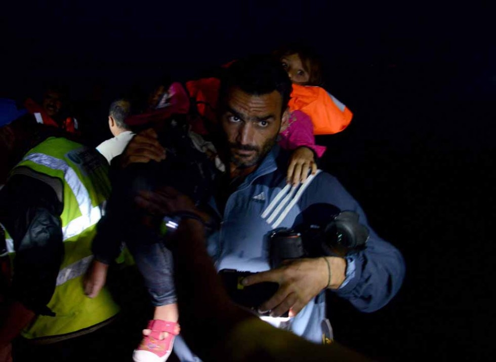 Aris Messinis carries a child in Lesbos in early October.