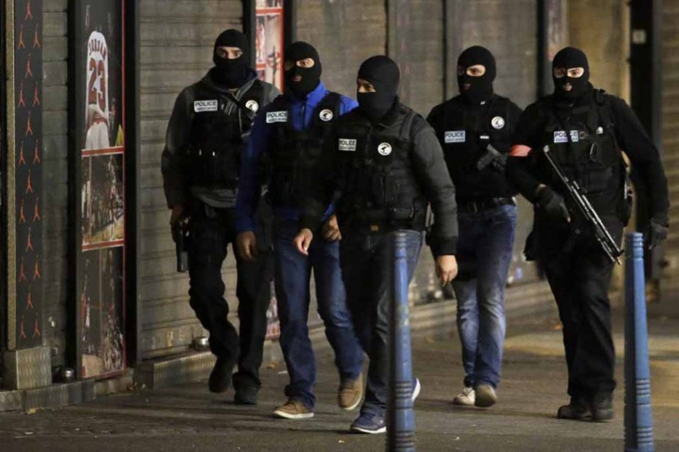 Masked French policemen in the Paris suburb of Saint-Denis as security forces raided an apartment in an operation targeting the mastermind of the attacks. (AFP/Kenzo Tribouillard)