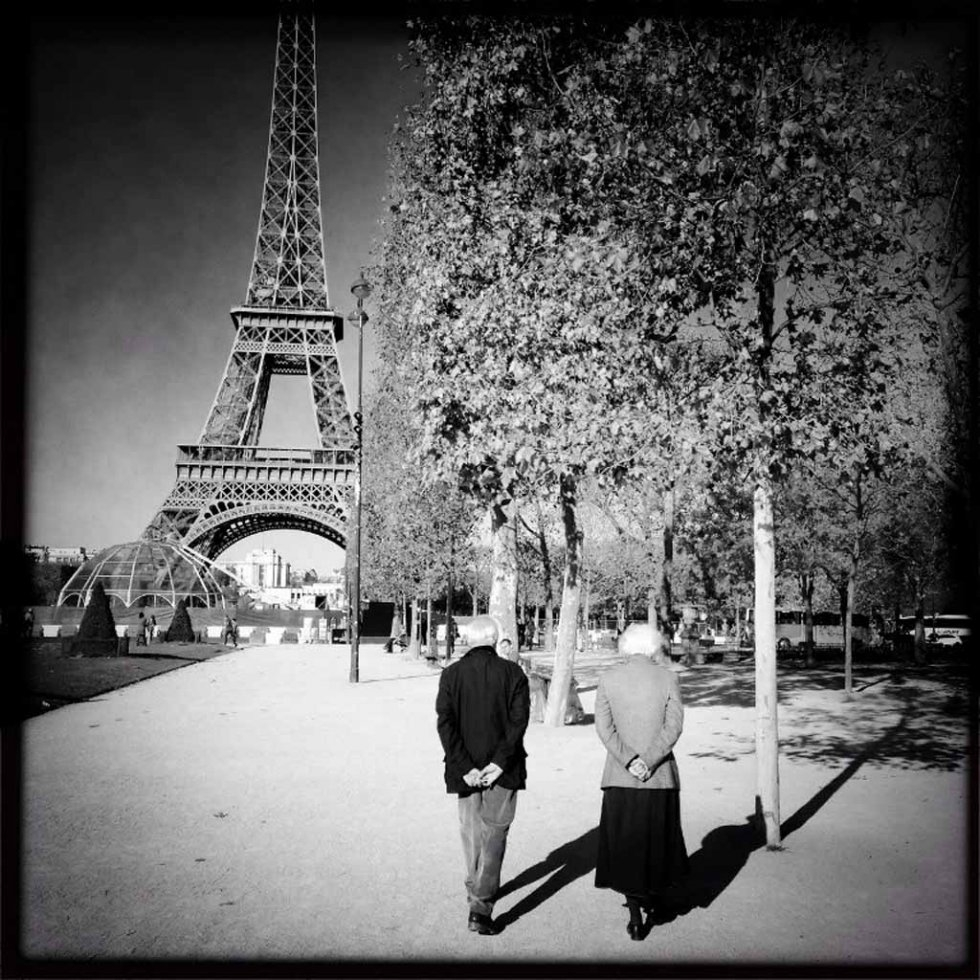 An elderly couple walks near the Eiffel Tower two days after the attacks.