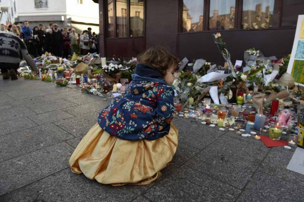 A child outside a memorial to victims at the Petit Cambodge restaurant. (AFP/Alain Jocard)