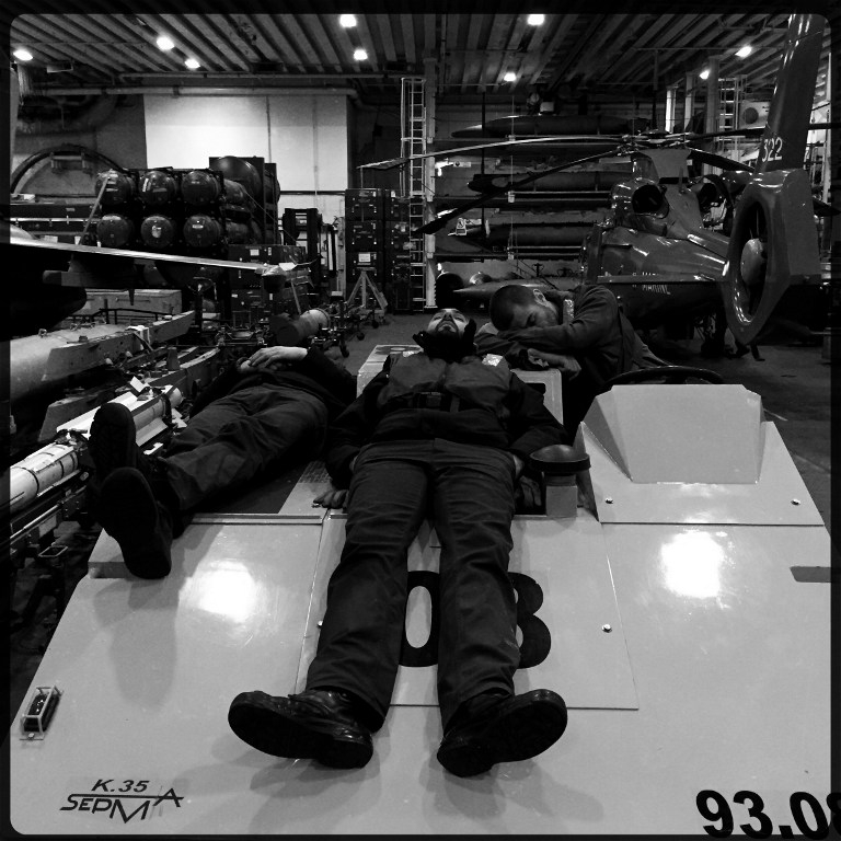 Rafale fighter jet technicians take a nap in the hangar of the Charles de Gaulle on February 25, 2015