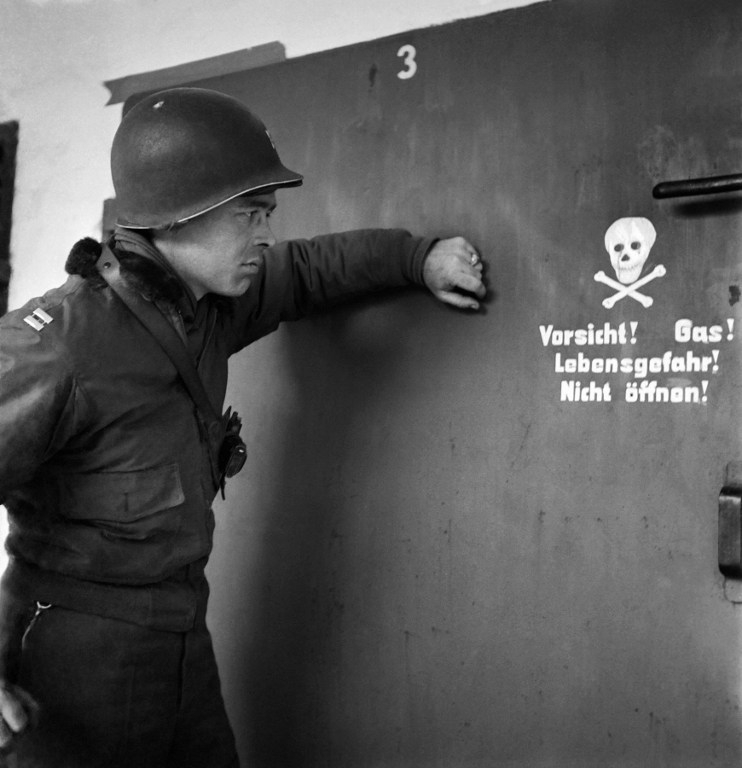 A US soldier before one of the gas chambers at Dachau in April 1945