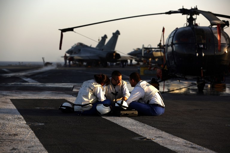 Catapult operators take a rest on the deck of Charles de Gaulle on February 26, 2015