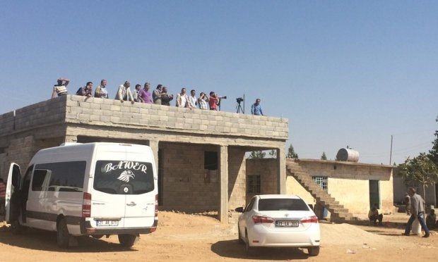 Locals gather on top of houses overlooking Kobane on the Turkish side of the border