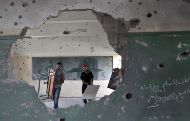 Workers carry tables in a classroom at a goverment school in Gaza City on September 13, 2014 one day before children go back to school