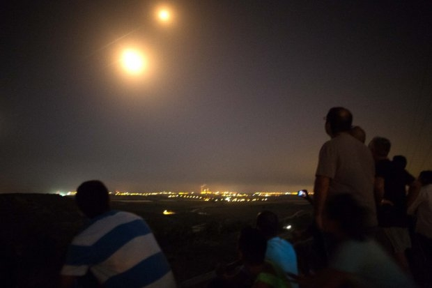 Israeli residents, mostly from the southern Israeli city of Sderot, stand on a hill overlooking the Gaza Strip, on July 12, 2014, to watch the fighting between the Israeli army and Palestinian militants