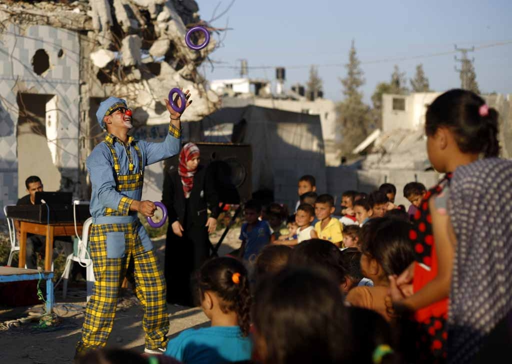 A clown performs for children in front of destroyed houses in Gaza City's Shujaiya neighbourhood on July 8, 2015