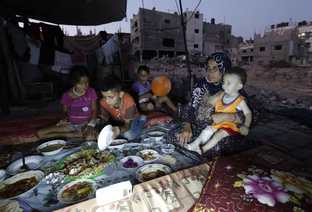 A Palestinian family gathers for the iftar meal breaking the Ramadan fast in the rubble of Beit Hanun, northern Gaza Strip on July 6, 2015