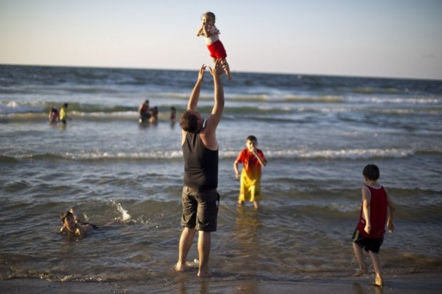 A Palestinian man plays with his baby on a Gaza beach on September 7, 2014