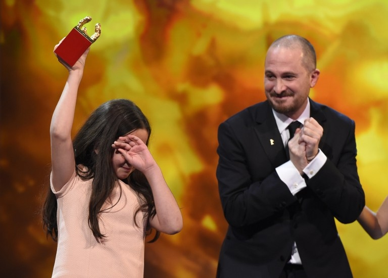 Jury head Darren Aronofsky looks on as Hana Saeidi accepts the Golden Bear best film trophy in place of her uncle, the Iranian director Jafar Panahi, at the Berlinale on February 14, 2015