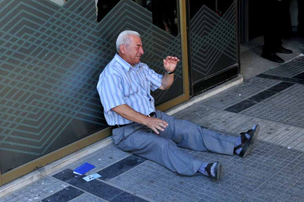 A July 3, 2015 photograph shows Greek pensioner Giorgos Chatzifotiadis crying outside a national bank branch in Thessaloniki (AFP PHOTO /SAKIS MITROLIDIS)