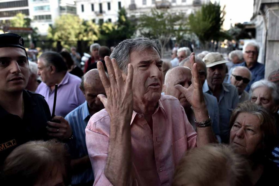 A man gestures as pensioners queue outside a national Bank branch, to cash out up to 120 euros in Athens on July 1, 2015 (AFP PHOTO / ARIS MESSINIS)