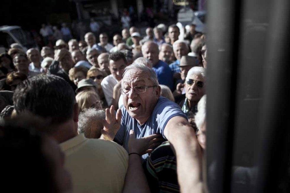 Pensioners try to enter a national Bank branch, as Greece reopened banks for pensioners who do not use cash cards for ATM, to allow them to withdraw their pension with a limit of 120 euros, in Athens on July 1, 2015 (AFP PHOTO / ANGELOS TZORTZINIS)