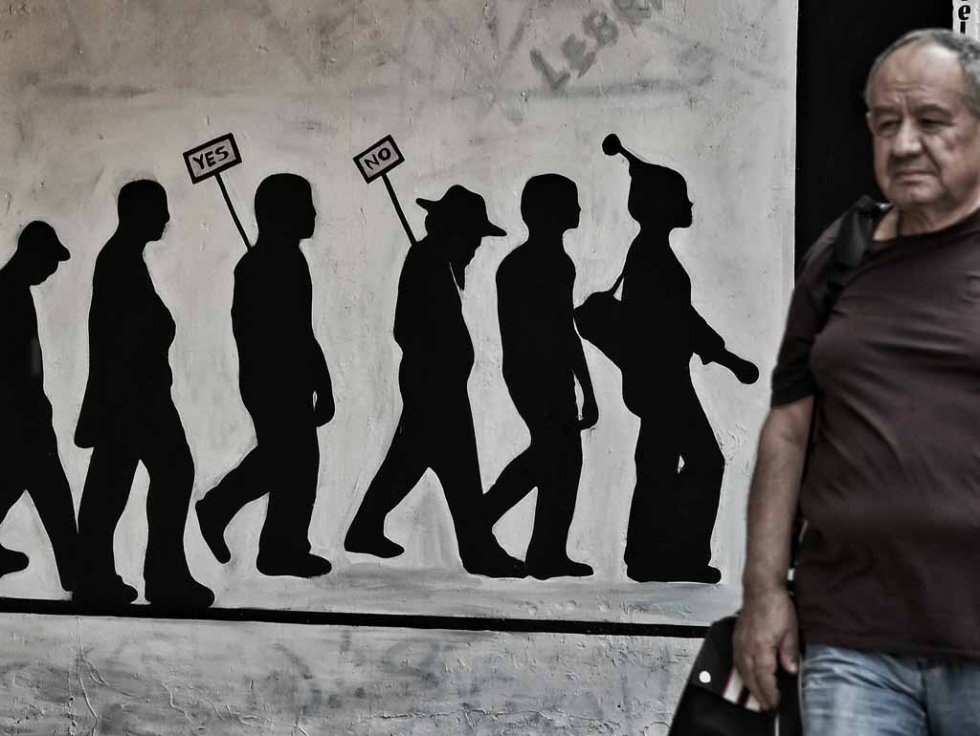 A man walks past a wall bearing graffitti concerning the Greek referendum a debt deal with its EU-IMF creditors in Athens on June 28, 2015