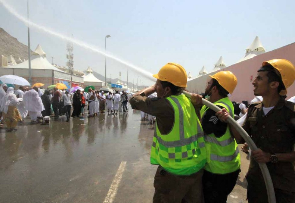 Saudi emergency personnel spray water to cool down the pilgrims in soaring temperatures.
