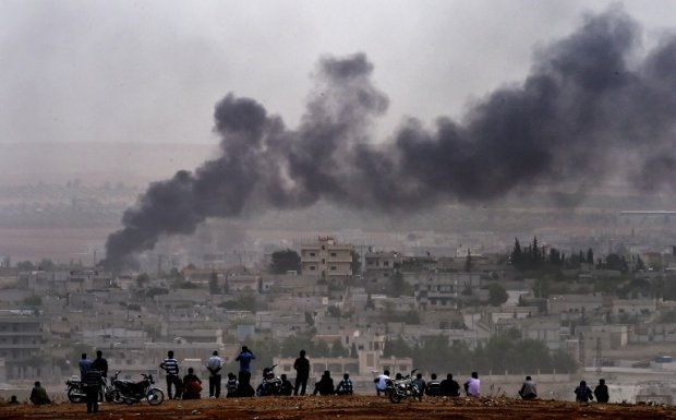 Kurdish people look at smoke rising from Kobane on October 11, 2014 (AFP Photo / Aris Messinis)