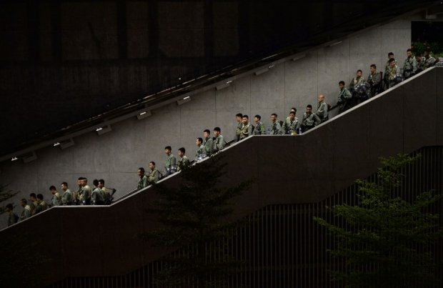 Police walk down a stairwell as pro-democracy demonstrators gather for a rally outside the Hong Kong government headquarters on September 29, 2014