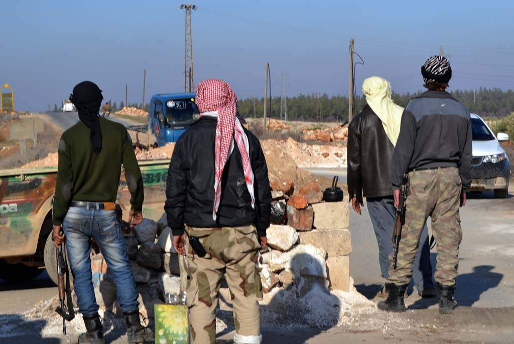 Rebel fighters man a checkpoint close to Jabal al-Zawiyaa in Syria's Idlib province in January, 2014
